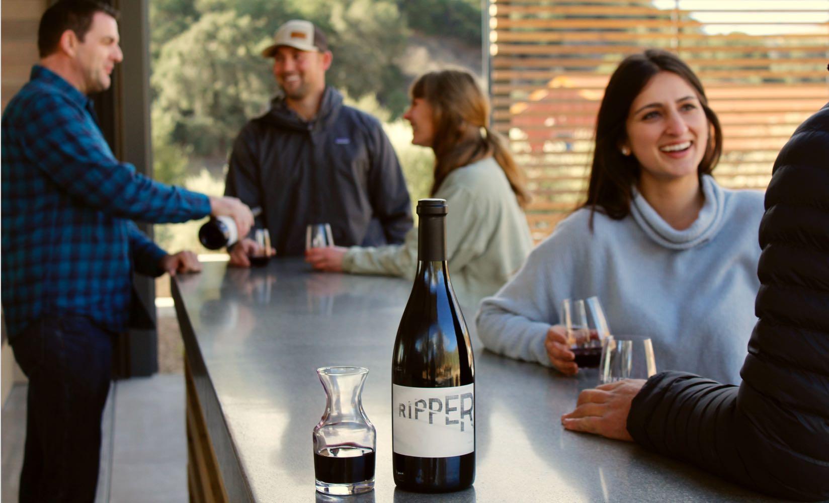 visitors wine tasting at the bar